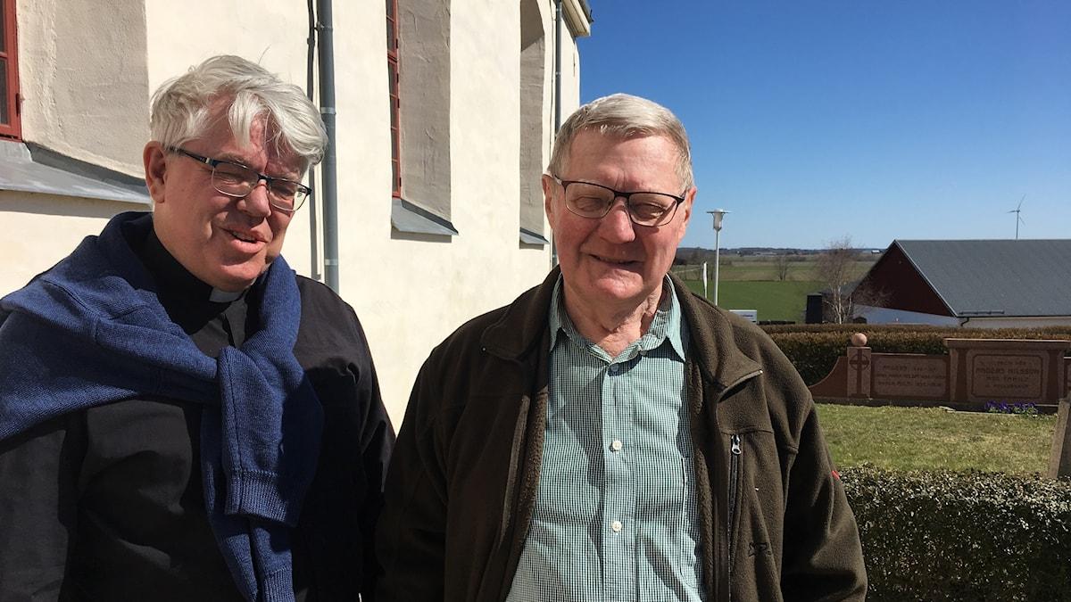 Präst Stefan Bjuvsjö och kyrkvärd Arne Ekholm utanför återuppbyggda Älvestad kyrka i Motala kommun.