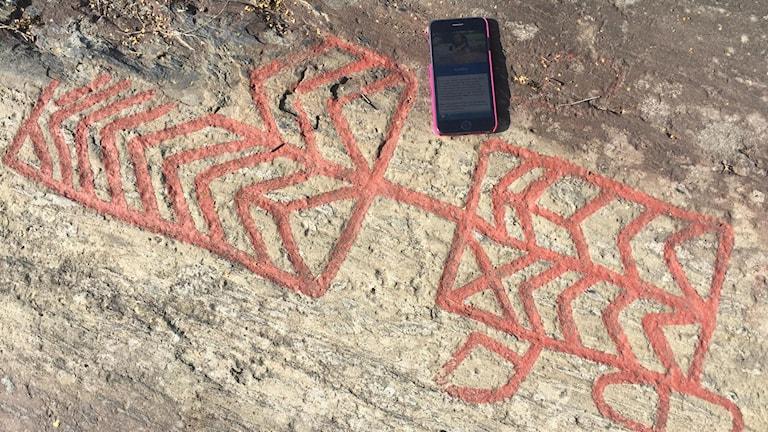 Hällristningar Himmelstalund med mobiltelefon.