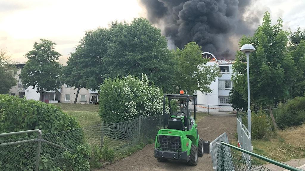 Brand i hus med traktor framför. Stort rökmoln.