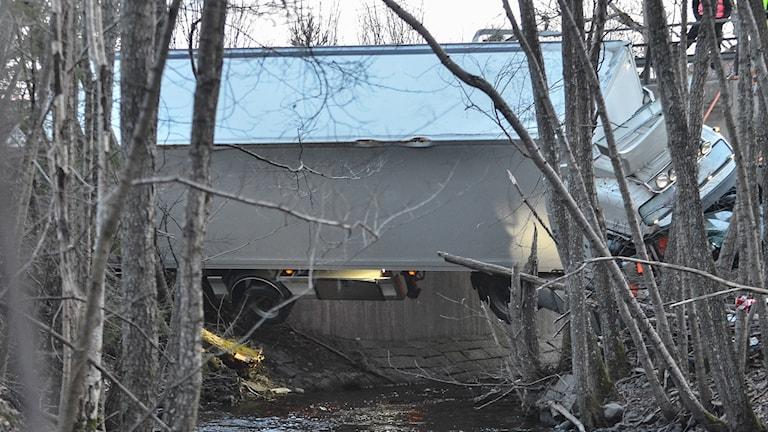 Lastbil som ligger tvärs över en å.