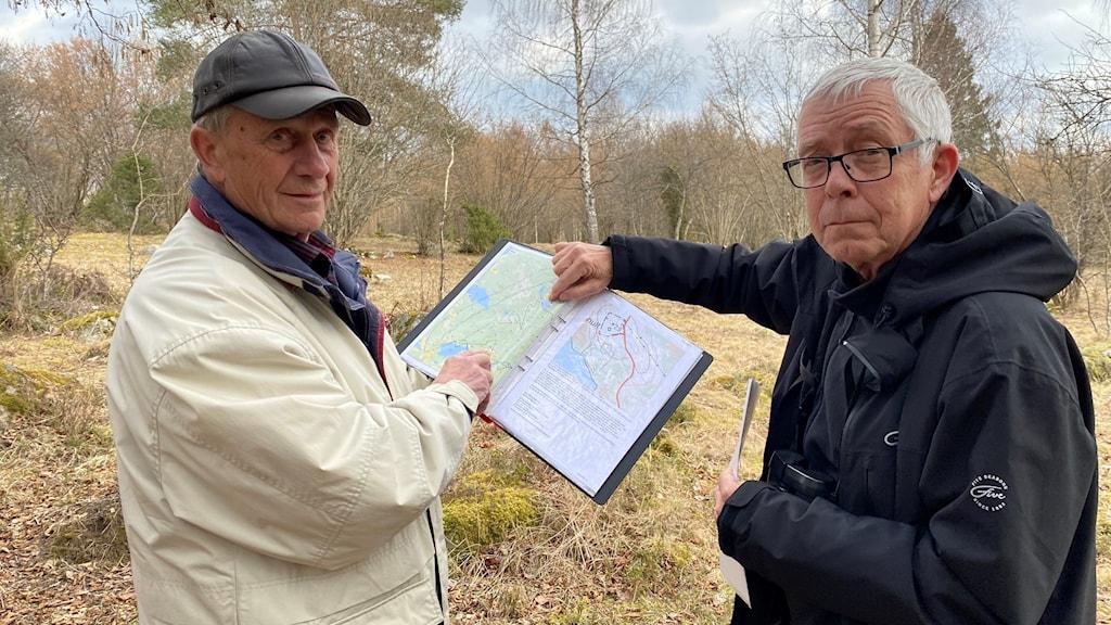 Kenneth Lekberg och Bo Tufvesson, ordförande i Naturskyddsföreningen i Finspång visar på kartan var Holmen vill bygga vindkraftverk. Här står de på ängen intill sjön Holmsjön.