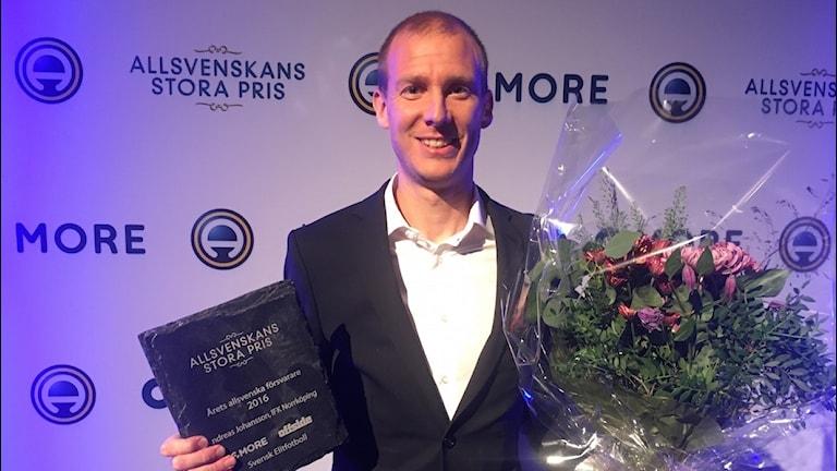 Andreas Johansson håller upp pris och blommor.