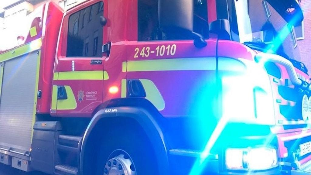 Bild på en räddningstjänstlastbil. Röd med blåljusen på.