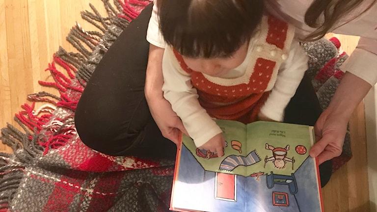 En mamma läser en bok tillsammans med sin dotter