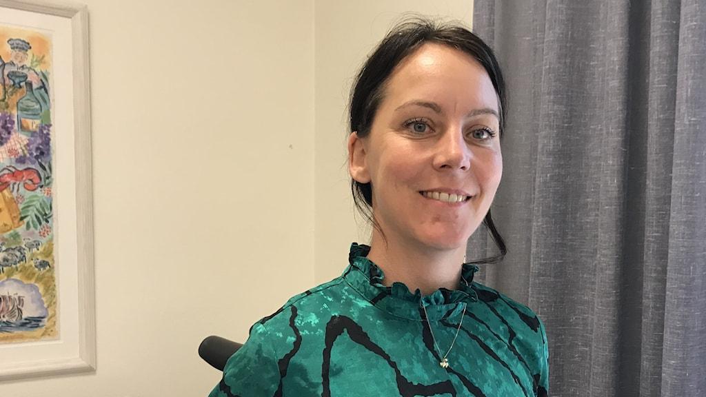 Hon har en grön blus med svart mönster. Står i ett av kommunens tjänsterum med en tavla och en beige gardin i bakgrunden.
