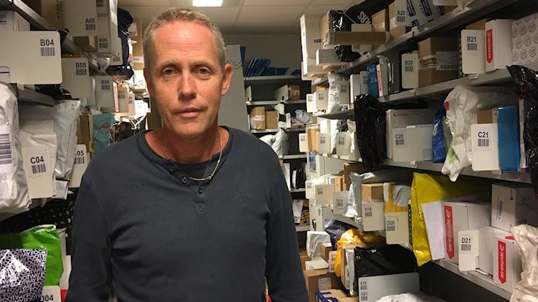Handlare Anders Skott i postrummet i sin matbutik. Paket på hyllor från golv till tak.