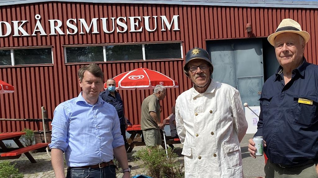 De står framför museet, en av dem har en gammal brandmanshjälm i svart med guldtext.