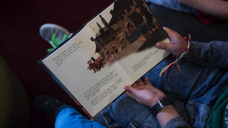 Barn läser i en bok.