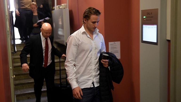 Ishockeyspelaren Jakob Lilja på väg in till rättegången i misshandelsmålet.
