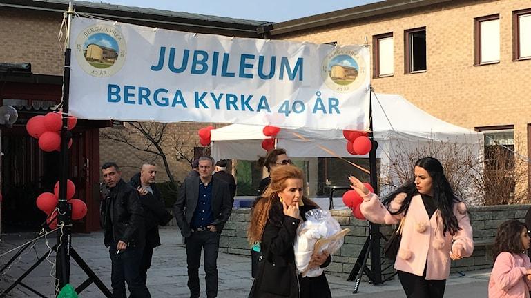 Besökare, ballonger och en stor banderoll utanför Berga kyrka.