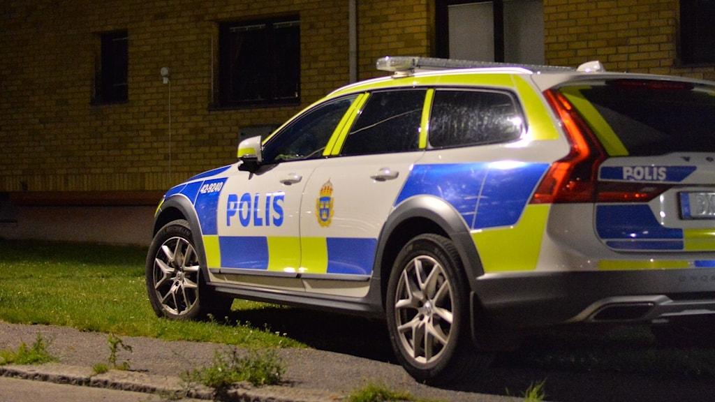 En polisbil står parkerad på snedden utanför ett tvåvåningshus, uppe på gräset. Det är mörkt ute.
