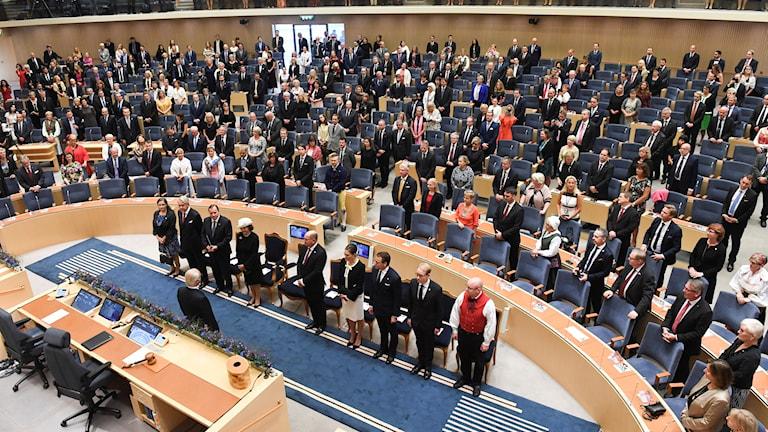 Riksdagsledamoterna och kungafamiljen ställer upp sig i plenisalen i riksdagshuset inför riksmötets öppnande.