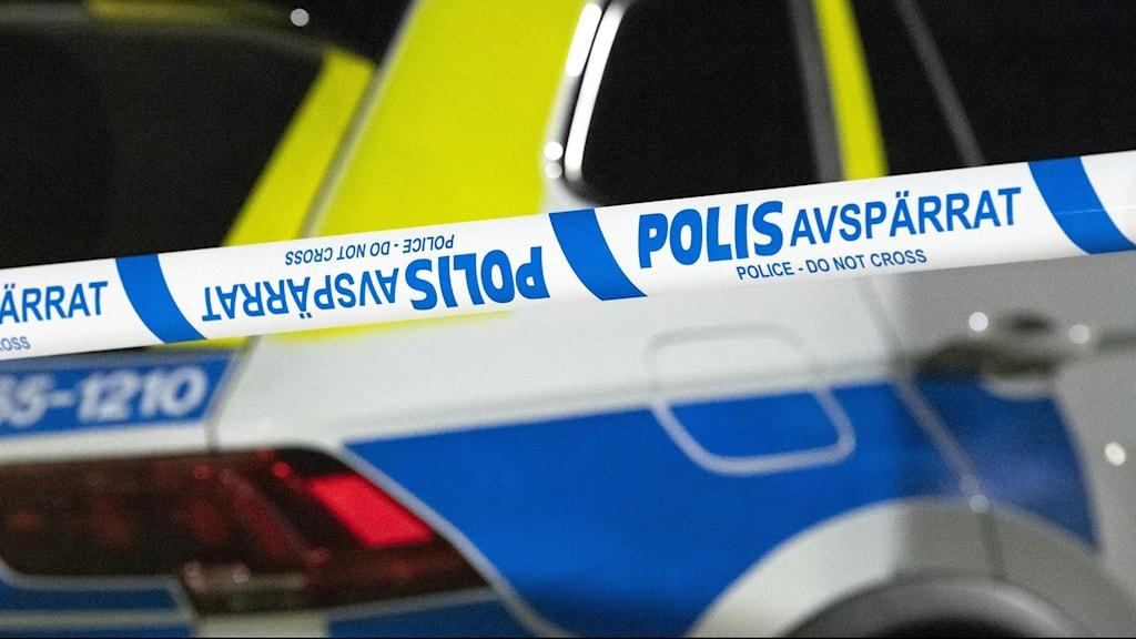 Polisbil bakom vit-blå avspärrningstejp.