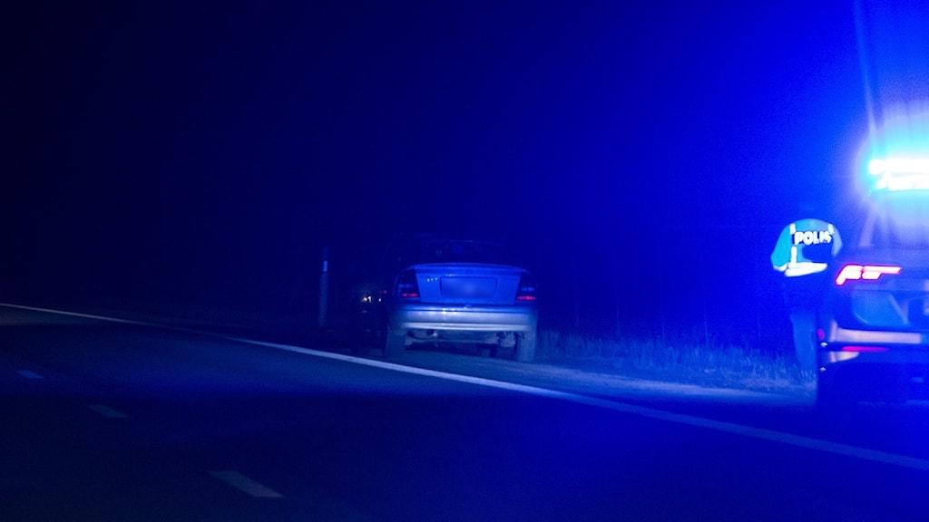 Polisbil med blåljus bredvid motorväg. Personbil stannad framför. Mörkt ute.