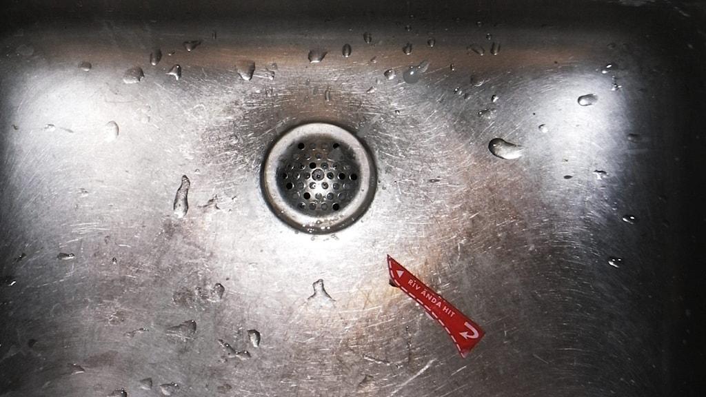 Närbild av en diskho där avloppet är i fokus och det syns även en avriven del av ett mjölkpaket.