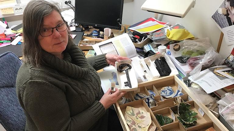 Arkeolog Ann-Charlott Feldt visar några av de 2099 fynden som gjorts vid utgrävningarna.