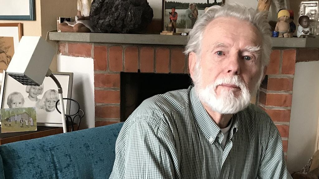 Johnny Ludvigsson, Linköping, senior professor och överläkare. Han sitter i en soffa framför en öppen spis i tegel i sitt vardagsrum.