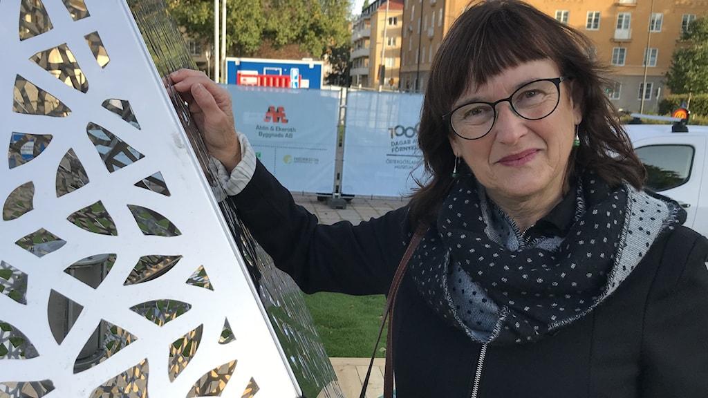 Hon står med ena handen lagd mot konstverket som är en tolvsidig kub i utklippt metallmönster.