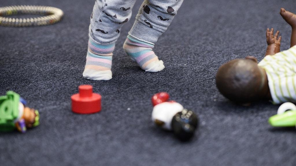 Ett barns fötter och leksaker