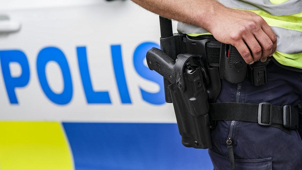 """Midjan på en polis i förgrunden, med ett pistolhölster. I bakgrunden syns ordet """"polis"""" på en polisbil."""