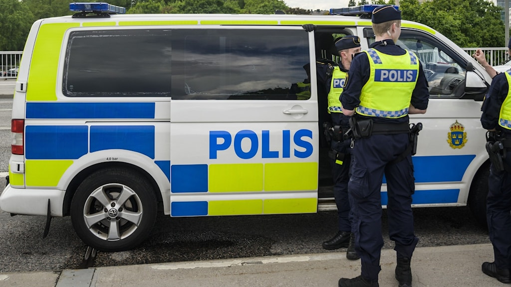 Närbild på en polispiketbuss och så syns även  två poliser med reflexvästar.