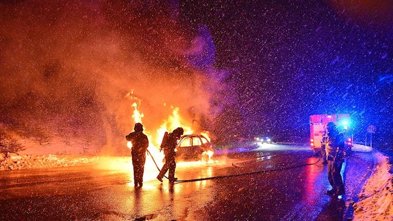 Räddningstjänstens personal bekämpar bilbranden.