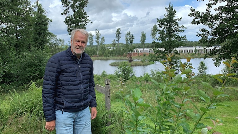 Äldre man står i lummig park på höjd framför en sjö.