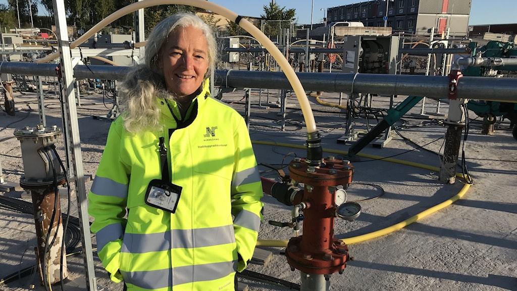 Elke Myrhede ansvarig för markmiljön vid inre hamnen i Norrköping, här vid ett av alla rör som värmer upp marken där lilla gasklockan legat. Hon har gul jacka. man ser massor med rör som löper från en betongen på marken och iväg åt alla håll.