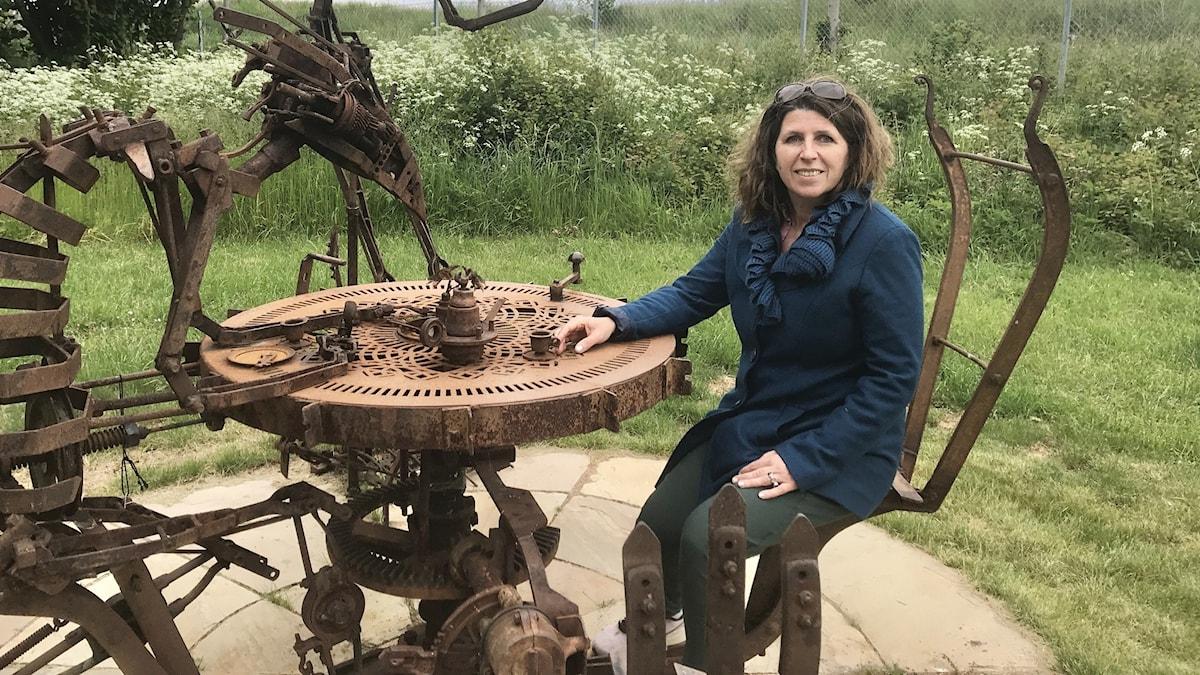 Ida Olai sitter i ett av konstverken i skulpturparken i Folkets park Vadstena.