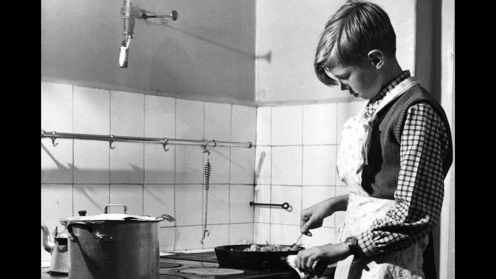 Skolpojke lagar mat vid spisen.