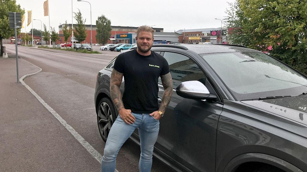 Man med tatueringar och svart t-shirt står framför bil, utomhus.