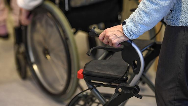 En kvinna med en rullator i halvfigur och en rullstol syns i bakgrunden.