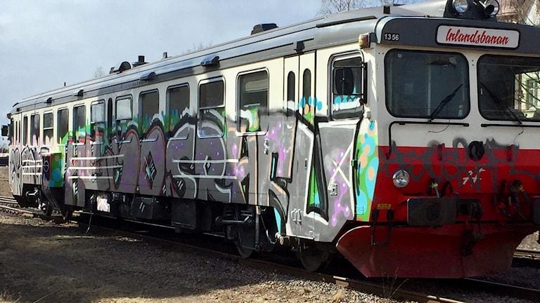 Pendeltåg med både klotter och grafitti på sidan.