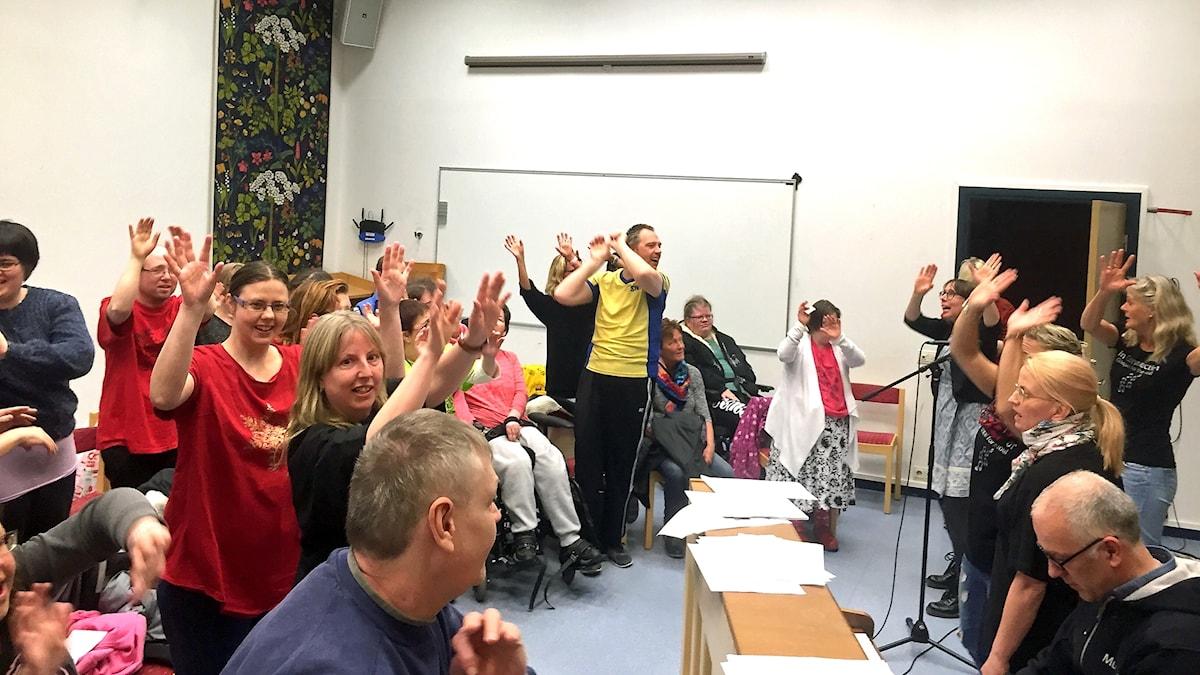 Flera människor sjunger och sträcker armarna upp i luften.