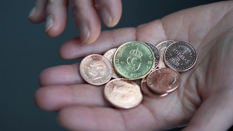En hand med ett gäng mynt i.