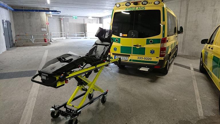 En bår framför en ambulans.