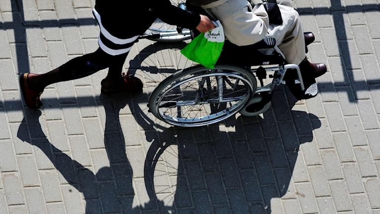 En personlig assistent kör sin brukare i rullstol