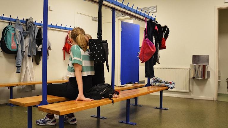 Två elever sitter i ett omklädningsrum.