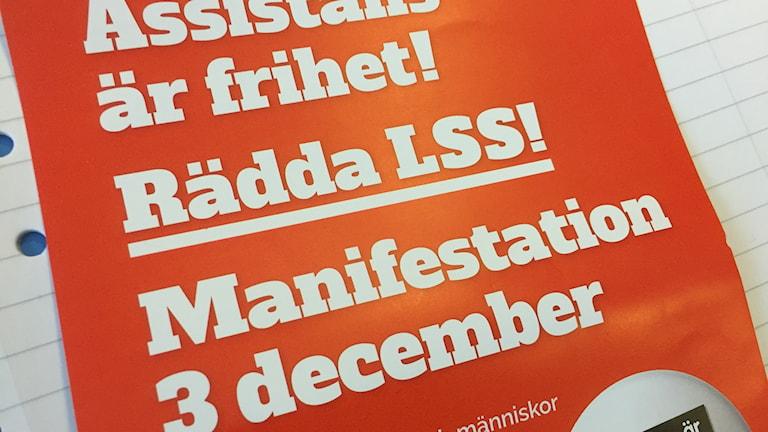En röd affisch med vit text om att det är manifestation 3 december för att rädda LSS.