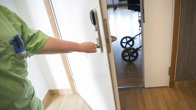 EN undersköterska på väg in i ett rum.