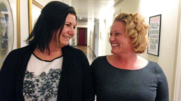Två kvinnor ler mot varandra.