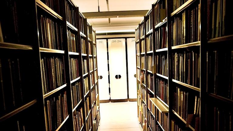 Två bokhyllor i ett mörkt bibliotek.