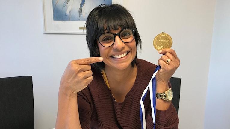 Jenny Hedlund visar upp en guldmedalj.