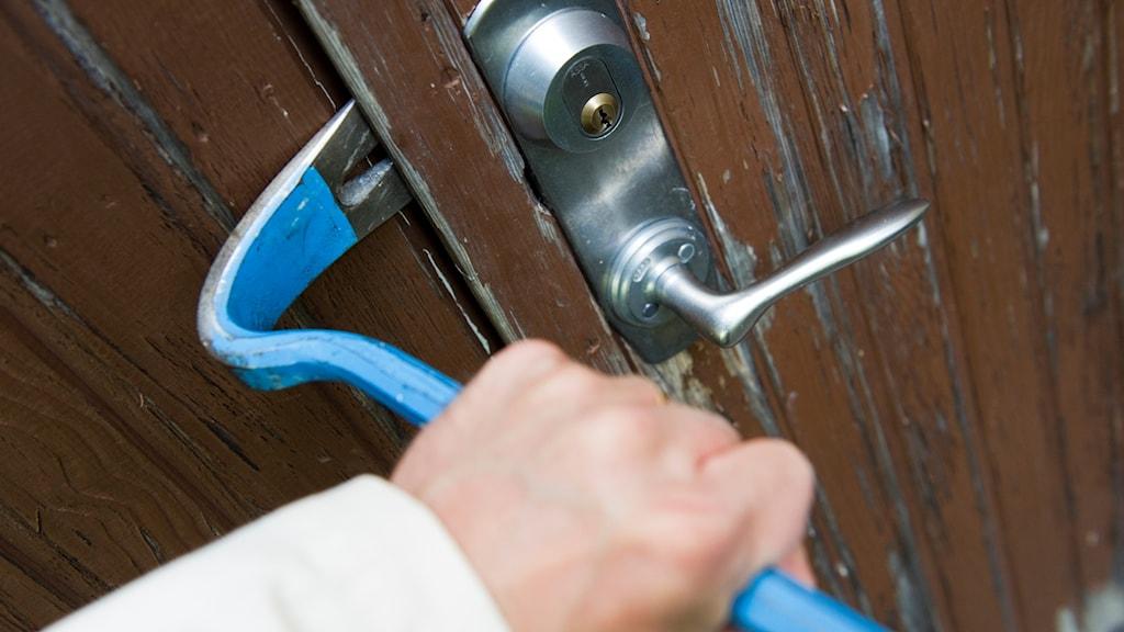 Någon bryter upp en dörr med en kofot.