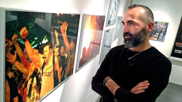 Fotografen Hossein Salmanzadhe står med armarna i kors och tittar på ett av sina färgstarka fotografier av protesterande människor.