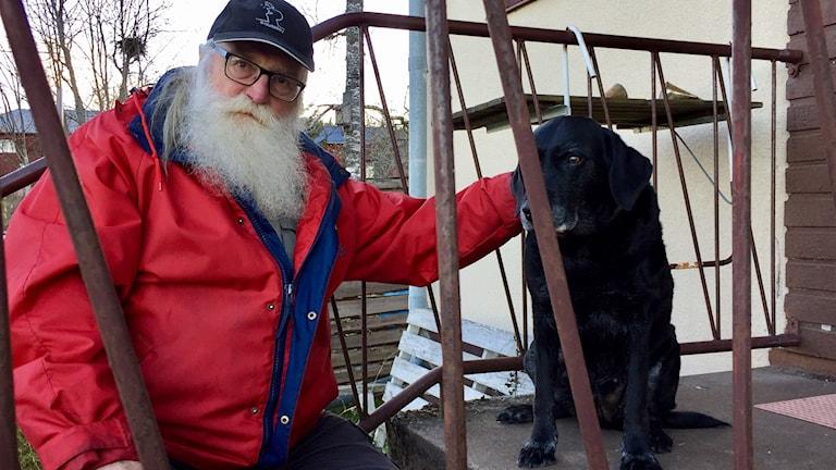 GöranTorin sitter på sin trapp tillsammans med labradoren Asta.
