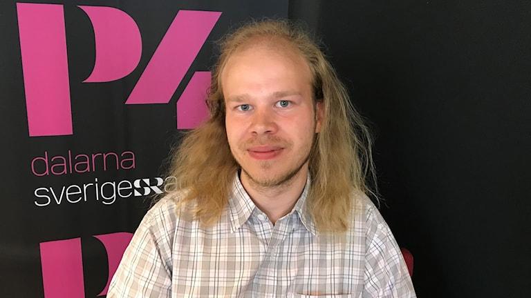 Fredrik Löfgren framför en svart vägg med ett rosa P4 Dalarna- tryck