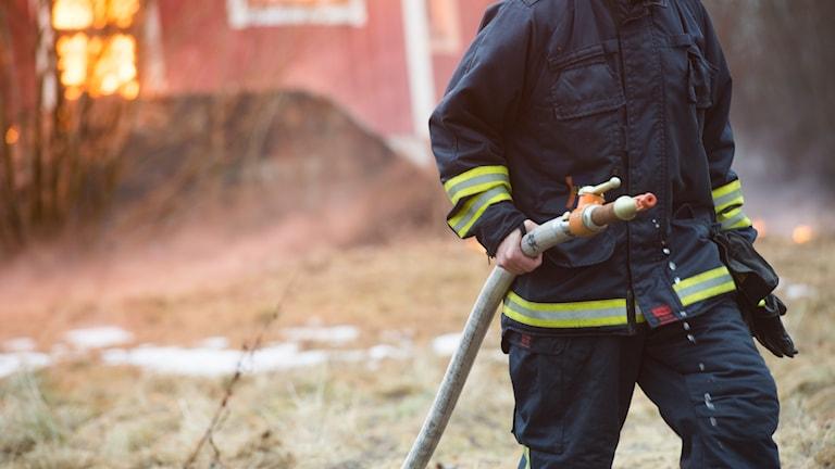 En brandman med vattenslang vid en husbrand.