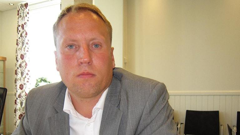 En bild på Jörgen Olsson, vd på Tunabyggen, som sitter i ett rum och tittar i kameran