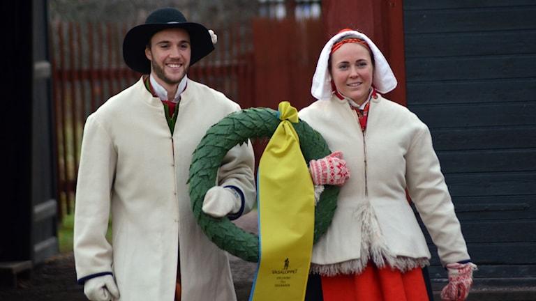 Man och kvinna klädda i Moradräkt bär en segrarkrans i armarna mellan sig.